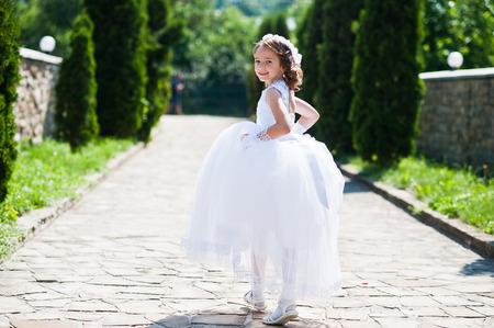 Portret cute little girl na białej sukni i wieniec z pierwszej komunii świętej tle tuja alei Zdjęcie Seryjne