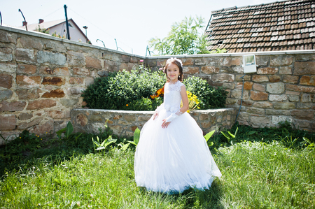 Portrait of cute little girl on white dress and wreath of first holy communion Stock Photo