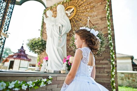 Portrait of cute little girl on white dress and wreath of first holy communion background monument of Holy Mary