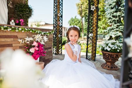 可爱的小女孩的肖像白色连衣裙和花环的第一圣餐的背景纪念碑的圣玛丽