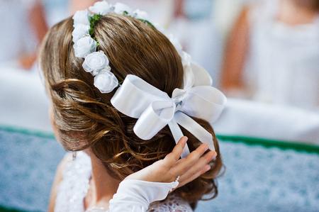 Witte boog en krans op kapsel van meisje op de eerste heilige communie