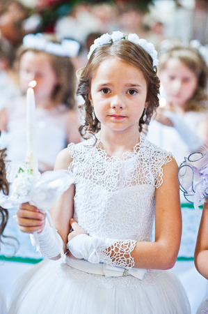 Portrait of cute little girl on white dress and wreath on first holy communion with burning candle at hands on church Stock Photo