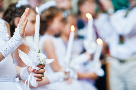 Hands with candles of little girls on first holy communion Stock Photo - 60126160