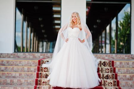 rubia ojos azules: La novia elegante ojos azules rubia de moda en la gran sala de bodas en la alfombra roja Foto de archivo