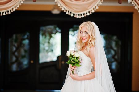 Elegant blonde blue eyes fashion bride at great wedding hall background curtains