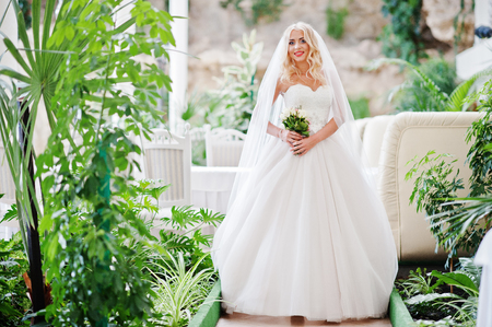 rubia ojos azules: Elegant blonde blue eyes fashion bride at great wedding hall with bouquet at hands