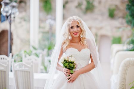 rubia ojos azules: La novia elegante ojos azules rubia de moda en la gran sala de bodas con el ramo en las manos Foto de archivo