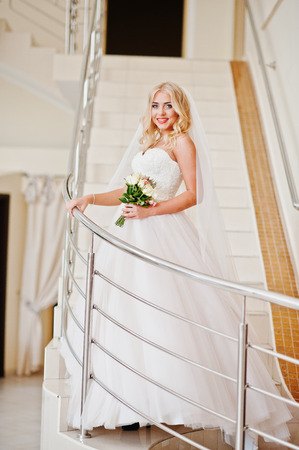 blonde blue eyes: Elegant blonde blue eyes fashion bride at great wedding hall on stairs with rail Stock Photo