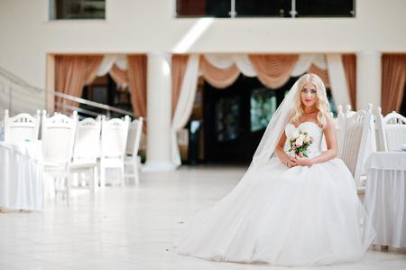 rubia ojos azules: Elegant blonde blue eyes fashion bride at great wedding hall sitting on chair