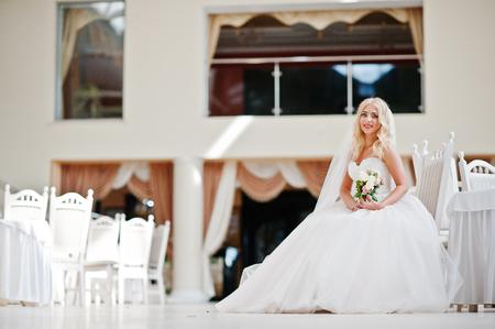 rubia ojos azules: La novia elegante ojos azules rubia de moda en la gran sala de bodas sentado en la silla