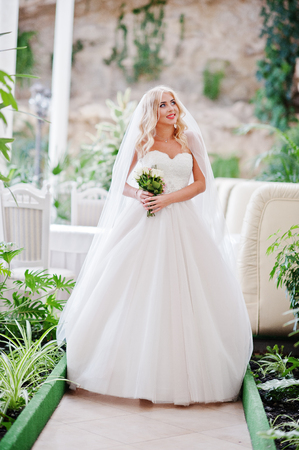 blonde blue eyes: Elegant blonde blue eyes fashion bride at great wedding hall with bouquet at hands