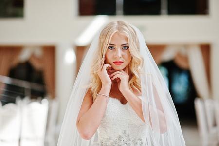 rubia ojos azules: Cerrar un retrato de la novia elegante rubia ojos azules de moda en un gran sal�n de bodas Foto de archivo