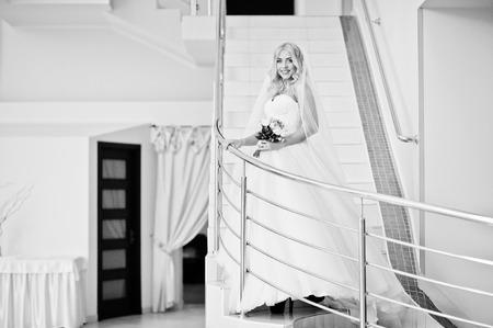 rubia ojos azules: La novia elegante ojos azules rubia de moda en la gran sala de bodas en las escaleras con ferrocarril