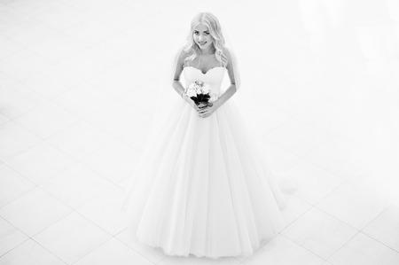 rubia ojos azules: La novia elegante ojos azules rubia de moda en la gran sala de bodas. En blanco y negro