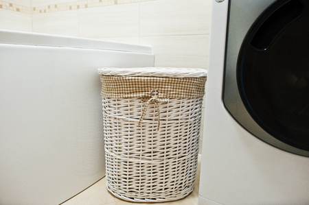 dirty clothes: White wicker basket for dirty clothes at bathroom
