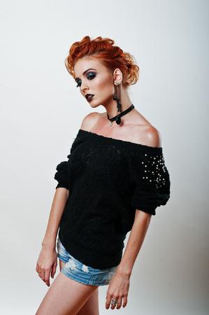 modelos posando: Retrato del estudio de la chica de pelo rojo en la blusa y pantalones vaqueros negros cortos con oscuro brillante compone