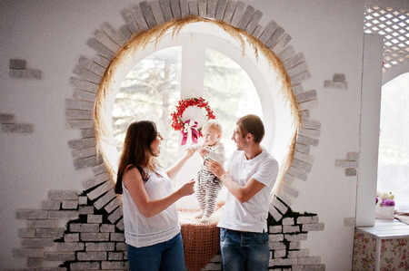 round window: Young caucasian happy family and baby boy background round window with decor