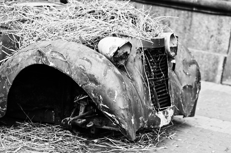 abandoned car: Old abandoned car with hay on engine