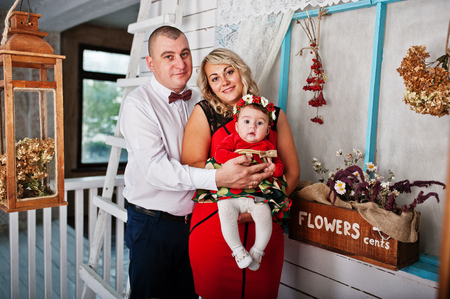 Father and mother with baby daughter posed at studio room