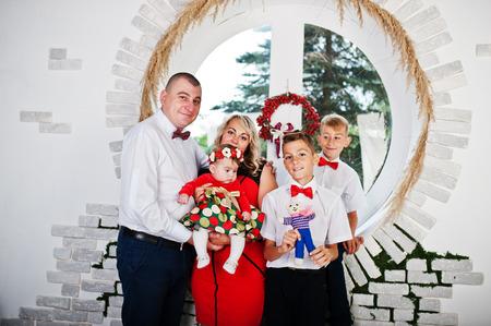 family  room: Caucasian family posed in vintage studio room background round window