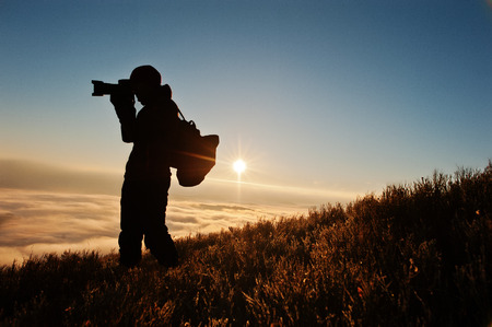sudetes: Silhouette of man photographer with camera on hand background mountains on sunset with fog. Amazing shot of beauty world and human.