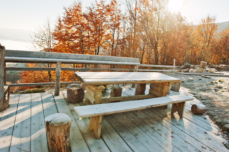 swept: Wooden frost table, benches and stumps on the terrace of teahouse on mountains