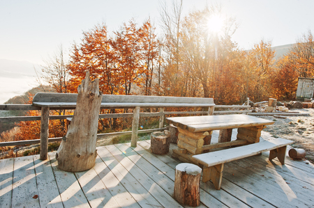 teahouse: Wooden frost table, benches and stumps on the terrace of teahouse on mountains