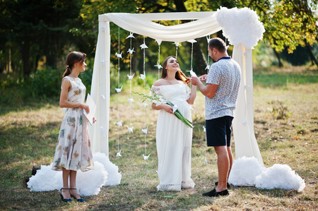 vows: Man read vows from paper for his pregnant woman and they future baby at ceremony background white arch on garden