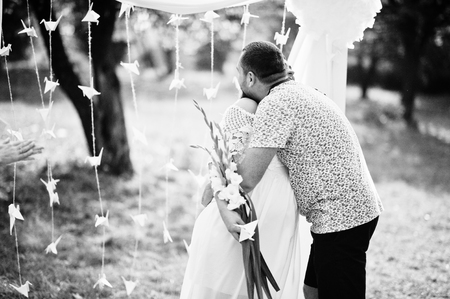 Man kiss and hugs his pregnant woman at marriage ceremony anniversary