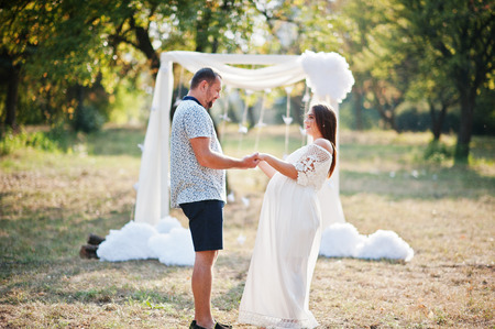 Happy pregnant couple stay hugging and loving near decor arch at garden on sunny day.