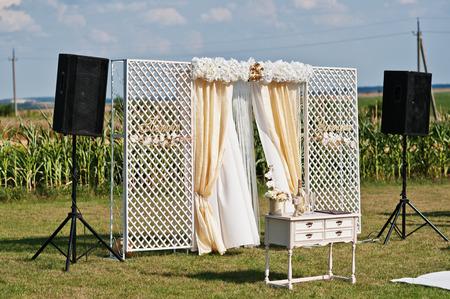 Bruiloft boog, wit tapijt met kleine tafel op wit en gouden tinten op trouw ceremonie.