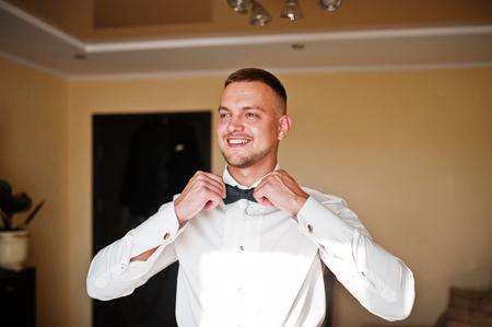 undone: Man wearing bow tie on shirt. Gathering of groom on wedding day.