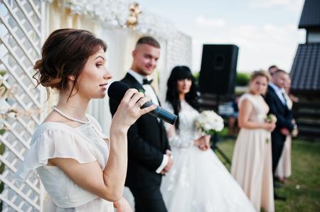 Master of ceremony speech on microphone background wedding couple. Stock Photo - 66153424