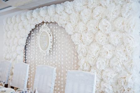Arche de mariage de décor blanc fleurs et cadre avec abréviation de noms de jeunes mariés.