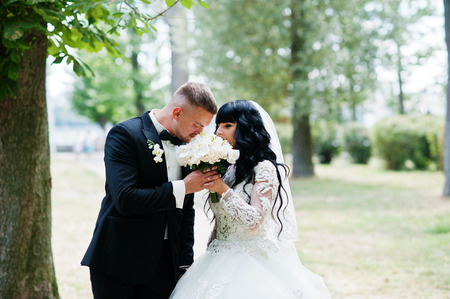 sniff: Adorable wedding couple at park sniff wedding bouquet. Stock Photo