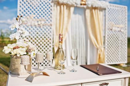 샴페인 잔과 촛대 배경 결혼식 아치와 신혼 부부의 표.
