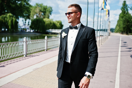 Elegant groom on sunglasses walking waterfront of lake with flag mock up at sunny wedding day. Foto de archivo