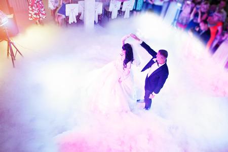 Erstaunlich ersten Hochzeitstanz newlywed mit verschiedenen bunten Licht und starken Rauch auf Restaurant. Blick von oben mit den Gästen.