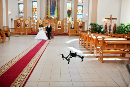 Kyiv, Ukraine - August 31: DJI Inspire Pro drone quadcopter recording on video wedding couple on church at wedding day.