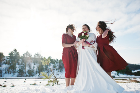 Pretty bridesmaids on red dresses with bride on sunny winter wedding day.