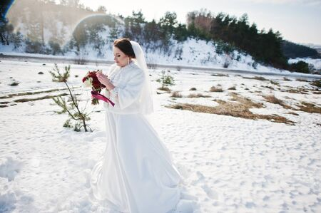 Portrait of cute brunette bride with bouquet on hands at frost and sunny wedding day.