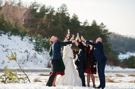 Best man with bridesmaids and newlyweds drinking champagne on frost winter wedding day. Stock Photo