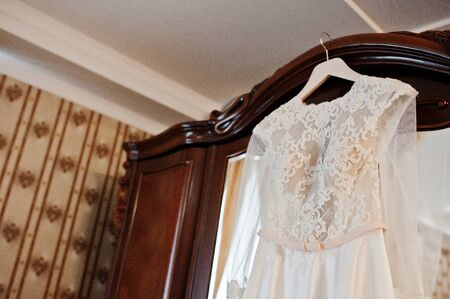 Amazing wedding dress on hangers at wooden closet on room of bride.