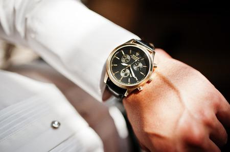 Hai, Oekraïne - 5 januari 2017: Man kijkt naar luxe horloges Rolex op zijn hand.