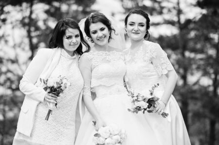 Pretty bride with bridesmaids on white dresses with bouquets on hands at wedding day. Black and white photo