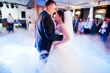 Amazing first wedding dance of wedding couple with heavy smoke and different lights. Blured bokeh effect. Stock Photo