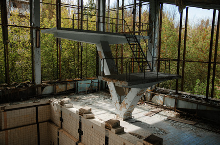 radiactividad: Lost school sport gym with swimming pool at Chernobyl city zone of radioactivity ghost town.