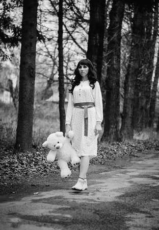 psychics: Young sad lonely brunette girl at sleepwear with soft toy bear on hands. Black and white photo.