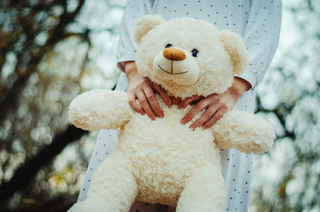 psychics: Soft toy bear on hands of girl on sleepwear outdoor. Stock Photo