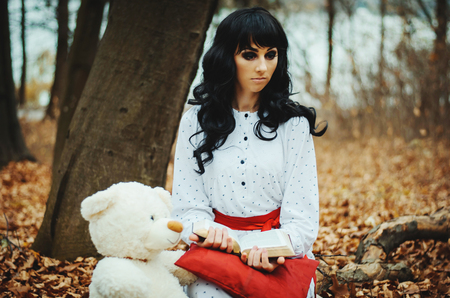 psychics: Young sad lonely brunette girl at sleepwear sitting on autumn forest and read book near soft toy bear.